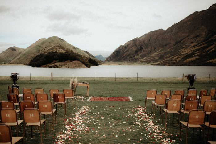 The wedding ceremony space was done with simple rustic chairs, petals and the amazing backdrop