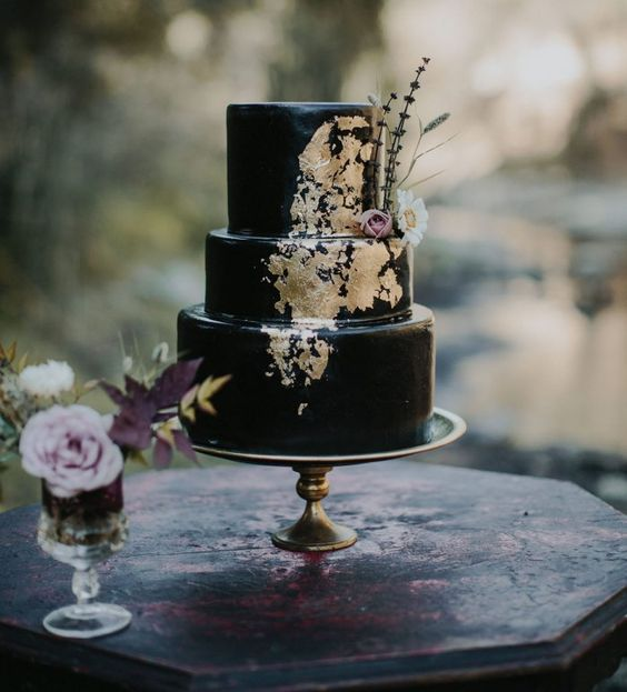 a black wedding cake with gold touches and feathers plus blooms is a classic Halloween idea