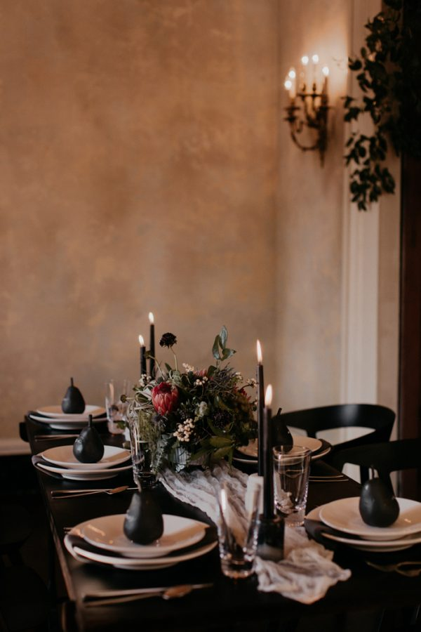 a chic table setting with a black table, a white table runner, black candles and pears plus a moody textural centerpiece