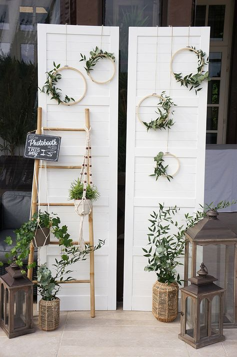 a natural rustic photo booth with an door backdrop, greenery, lanterns and wicker vases
