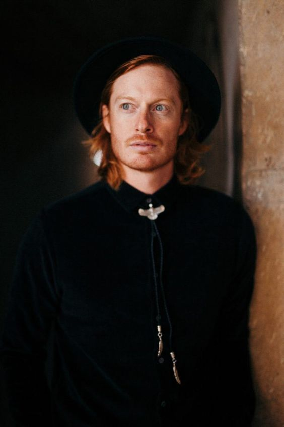 a relaxed look with a boho feel with a hat, a black velvet shirt, a bolo tie with a bird