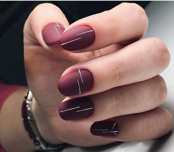 matte burgundy nails with thin white stripes is an ultra modern take on usual wine shades