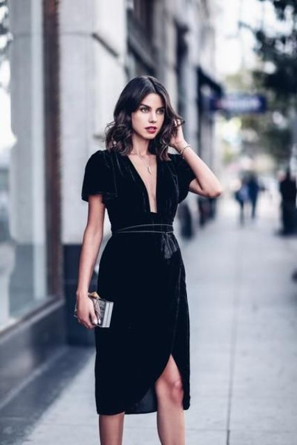 a black velver knee wrap dress with a plunging neckline and a tassel sash looks wow