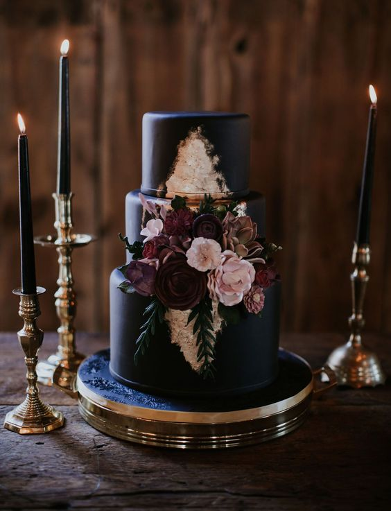 a black wedding cake with touches of gold and sugar flowers for decor is classics not only for Halloween
