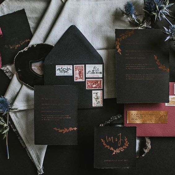 a black wedding stationery suite with copper foil, vintage stamps and a burgundy envelope