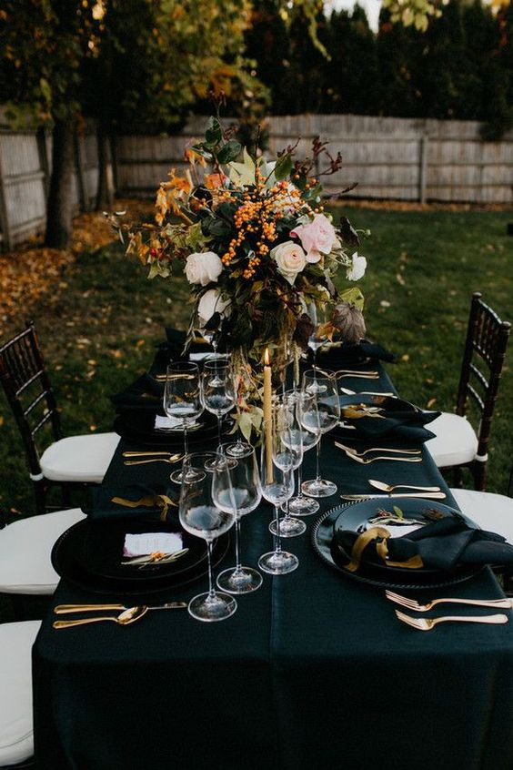 a chic tablescape with a black tablecloth, napkins, gilded touches and a lush floral centerpiece with berries