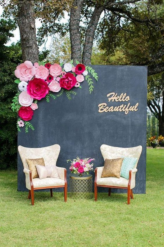 a simple photo booth with a chalkboard wall with pink paper blooms and comfy chairs