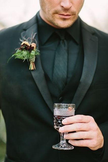 a total black groom's look with a moody burgundy and yellow boutonniere for a wow effect