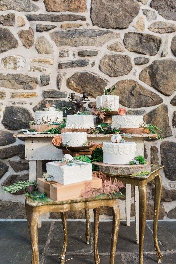 a whole arrangement of wedding cakes on a large table and several smaller vintage ones