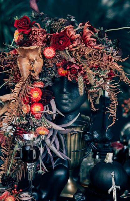 a wicked wedding centerpiece of a human bust topped with lush blooms in deep red, burgundy flowers and cascading dried greenery
