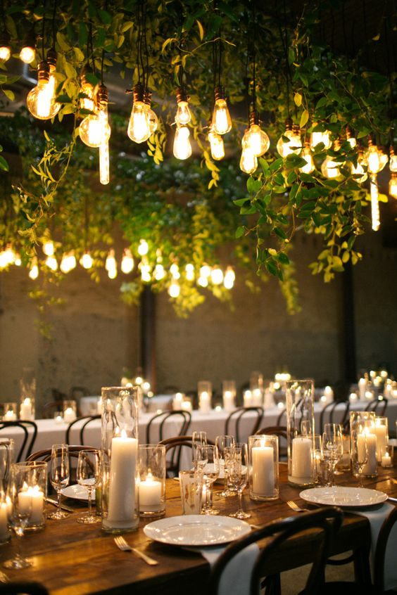 overhead wedding decor with lots of fresh greenery and bulbs hanging down