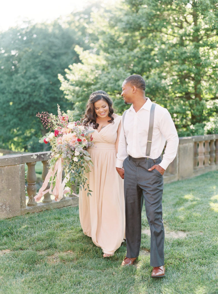 The bride was wearing a blush wedding dress with a deep V-neckline and a delicate hair vine