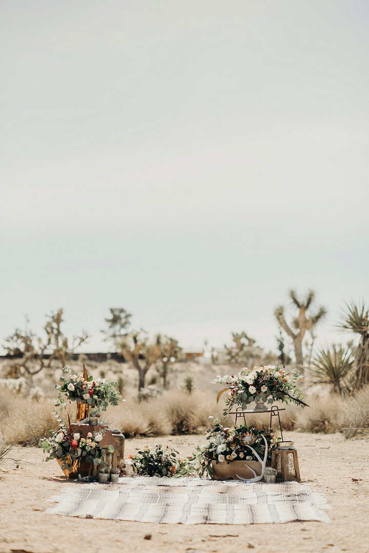 The ceremony space was done with boho rugs, antlers, stones, lanterns and lush greenery and blooms