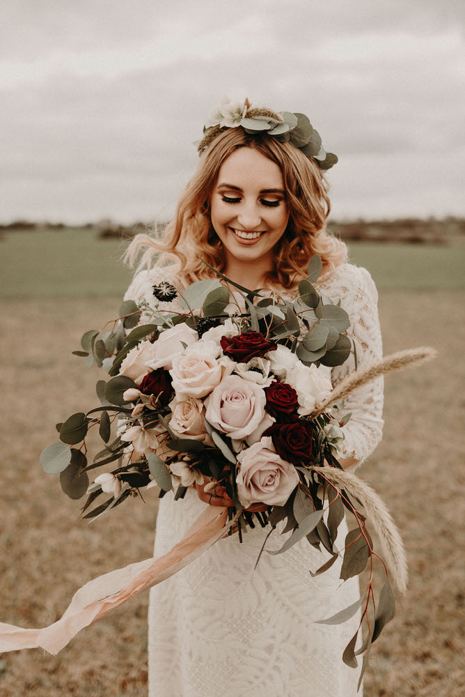 The wedding bouquet was done with white, blush and burgundy blooms plus grasses