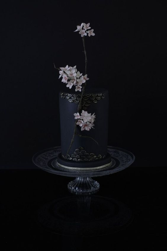 a breathtaking matte black wedding cake with gilded scales and real sakura flowers for decor