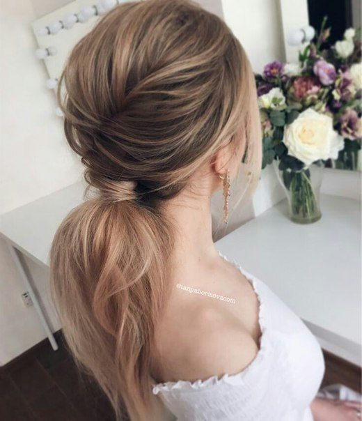 a messy voluminous ponytail with a bump and some locks to frame the face