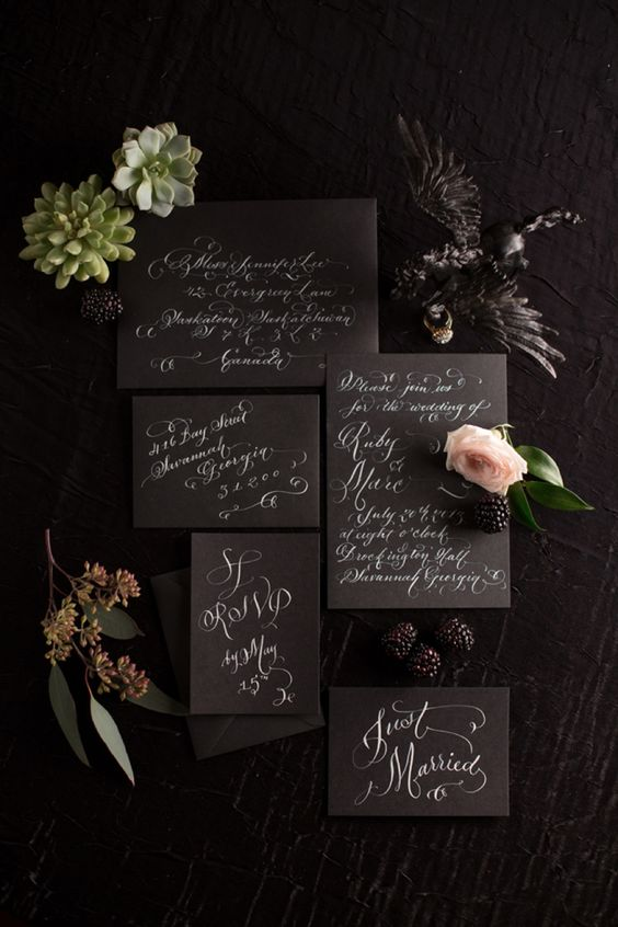 a moody black and white invitation suite with calligraphy for a modern Halloween wedding