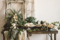 05 a rustic garden wedding dessert table with plenty of greenery and blooms and vintage frames plus lace