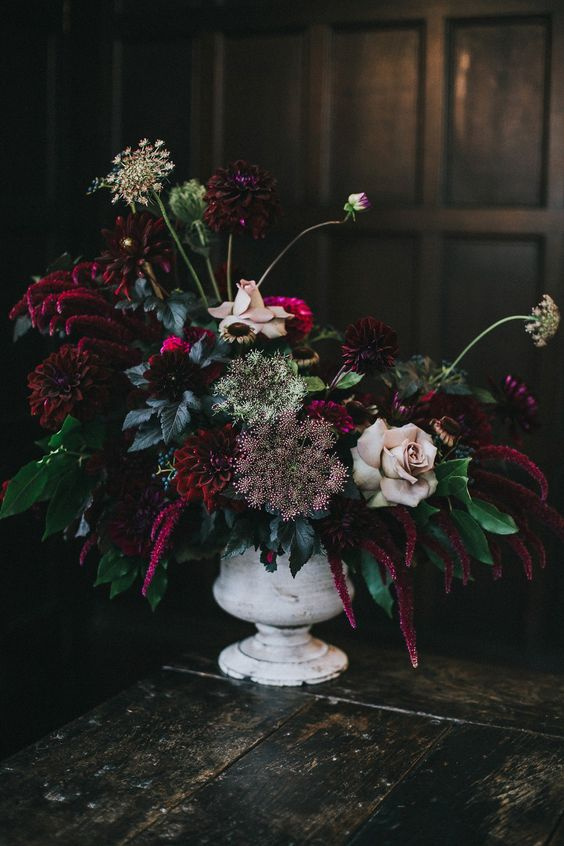 a vintage whitewashed vase with deep purple and burgundy blooms, pale rosesm herbs and greenery