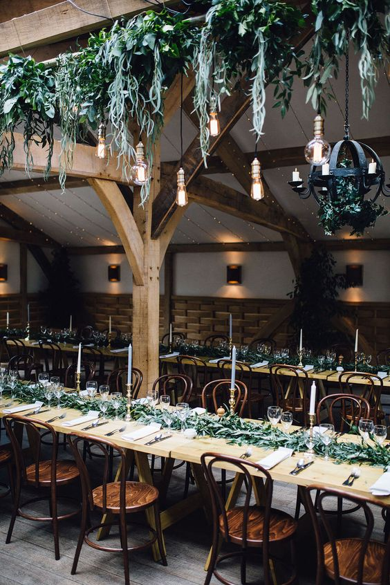 overhead wedding decor with cascading greenery, bulbs and a sphere candle chandelier