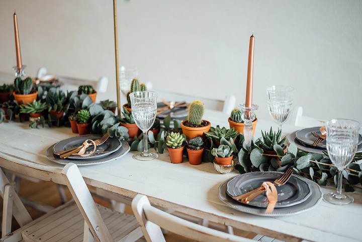 The wedding table was lined up with potted cacti and succulents plus copper candles