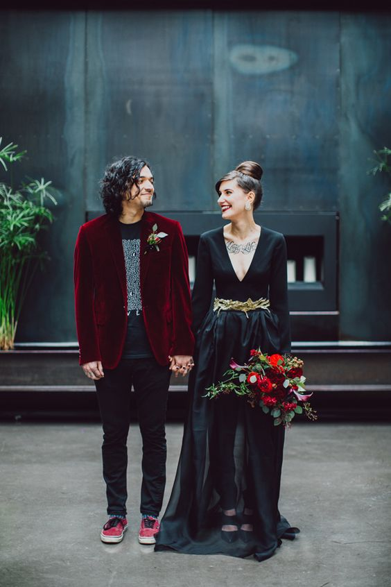 a black wedding gown and a black look spruced up with a deep red velvet blazer for the groom