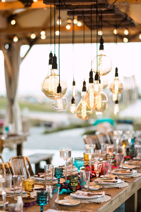 a boho tablescape with large bulbs hanging over it for more light and an industrial feel