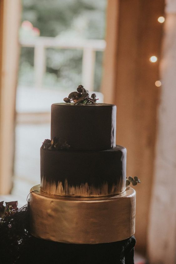 a chic black and gold Halloween wedding cake topped with berries and foliage is a bold modern solution