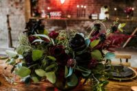 06 a dark burgundy and black roses centerpiece with greenery and eucalyptus is classics for Halloween