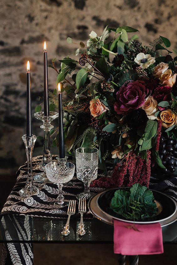 a dark wedding table setting with black candles, a black printed table runner, a pink napkin, a lush floral centerpiece and greenery