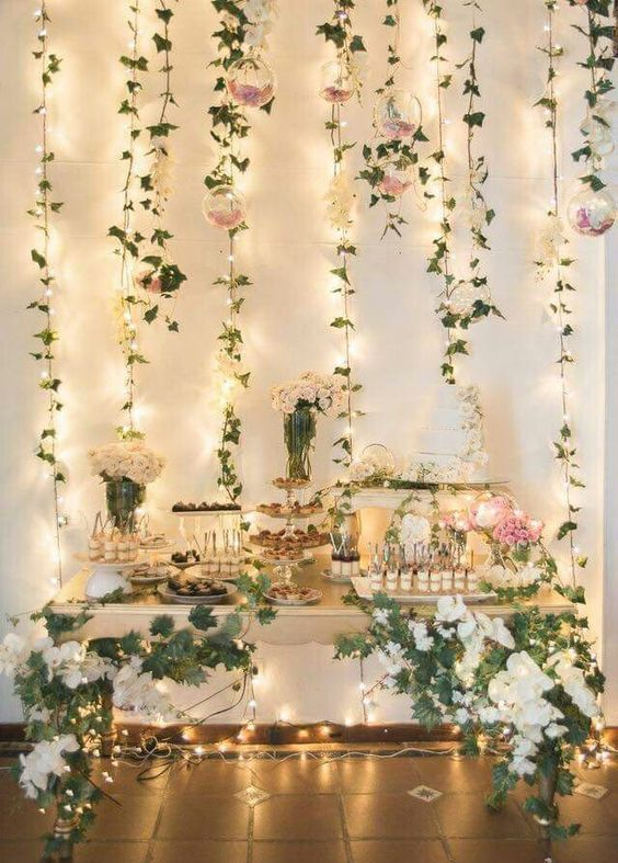 a lush spring garden dessert table with lights and hanging greenery and blooms in pink and white