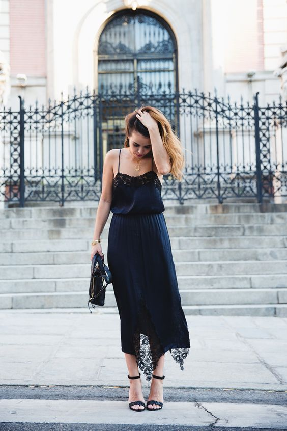 a navy slip dress with black lace inserts and black heeled sandals for a statement