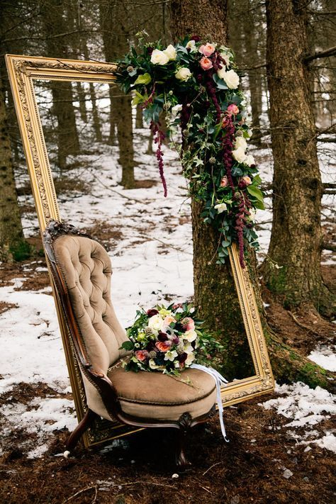 a romantic outdoor photo booth done with a vintage gilded frame with lush blooms and a refined chair