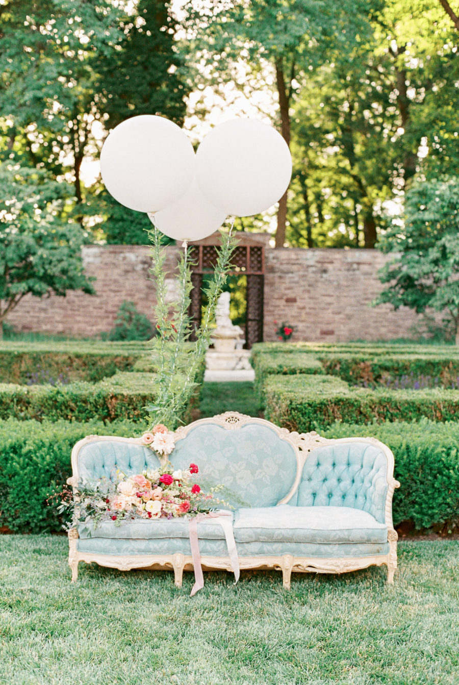 The beautiful garden was spruced up with a refined blue sofa and white baloons
