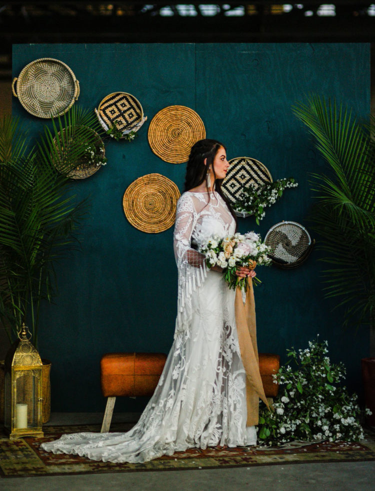 The wedding backdrop was a teal wall with woven baskets and greenery