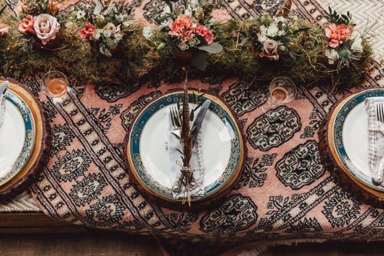 The wedding tablescape is done with boho fabric, a moss runner with blooms and wood slice chargers