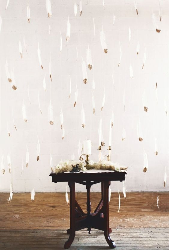 a beautiful and airy white and gilded feather backdrop is a chic ethereal idea  for any wedding