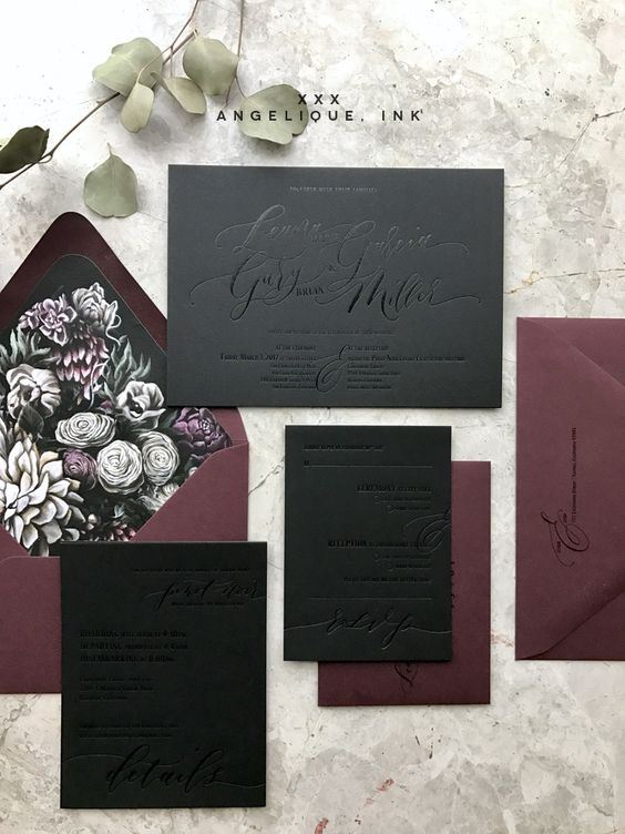 a black and plum-colored wedding invitation suite with dark floral lining and pressed calligraphy for a moody wedding