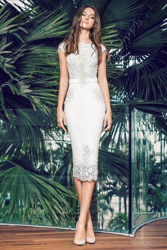 a chic lace embellished sheath wedding dress with cap sleeves and an embellished sash for a modern romantic bride