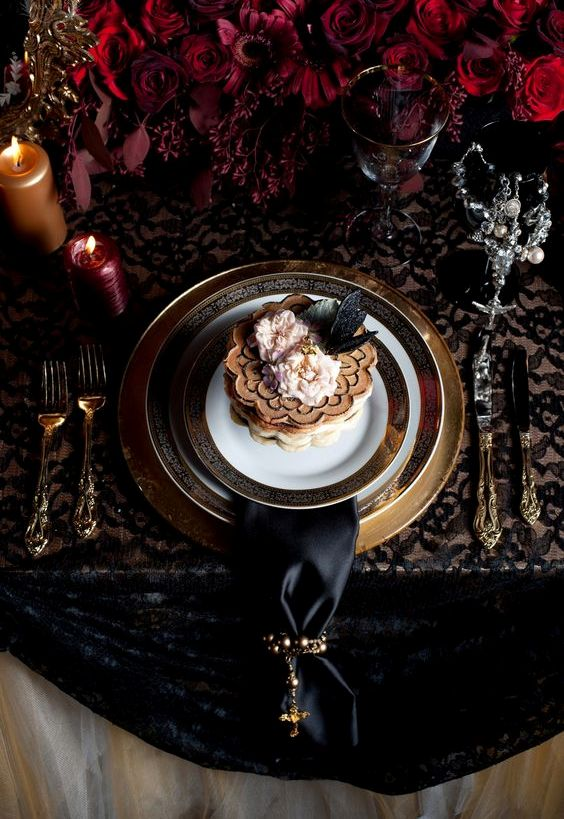 a luxurious wedding tablescape with lush deep red florals, candles, gilded touches and a black napkin