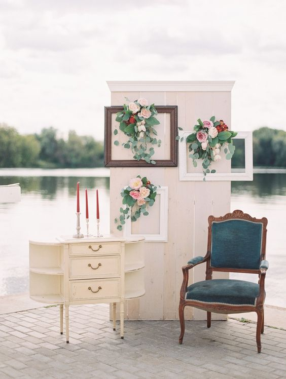 a peaceful lake photo booth with frames, blooms, a vintage dresser, candles and a blue chair