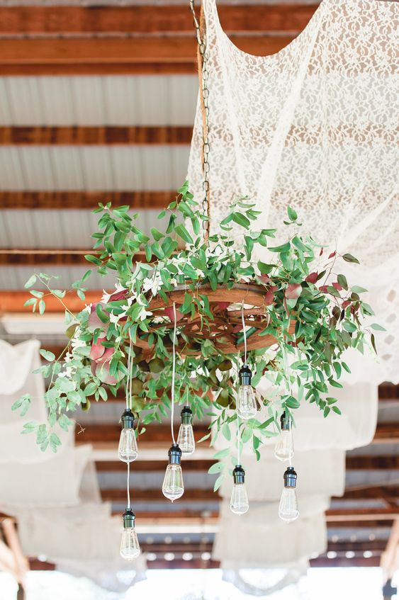 a rustic wedding chandelier of an old wheel, fresh greenery and bulbs hanging down