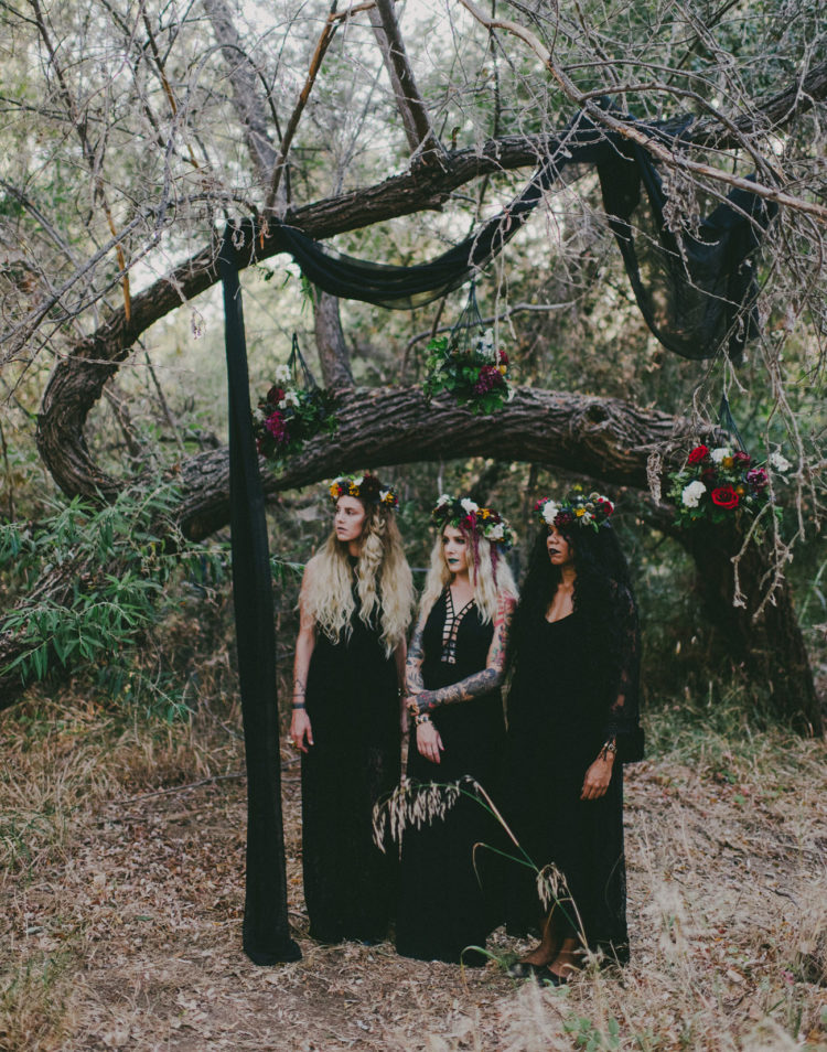 bridesmaids wearing mismatched black gowns and colorful floral crowns for the bridal shower