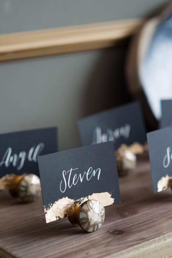 chic black escort cards with calligraphy and gold foil