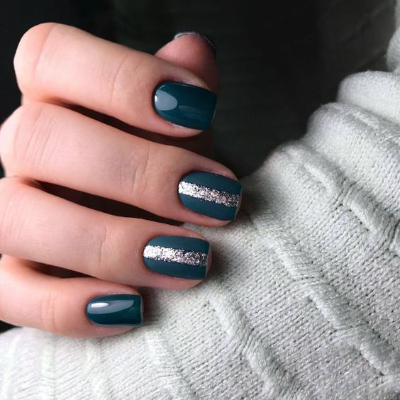 shiny and matte teal nails with silver glitter stripes in the middle to embrace the season and make a colorful statement