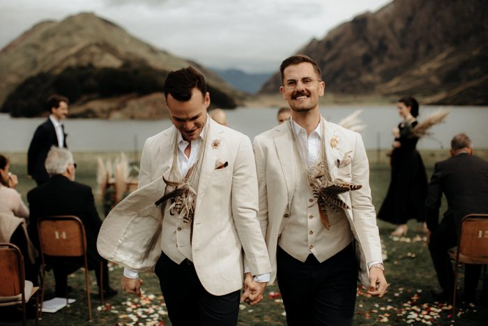The grooms rocked feather necklaces after the ceremony for fun