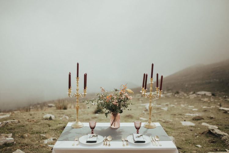 The tablescape was modern yet wild, with a grey table runner, burgundy candles, gilded touches and colored glass