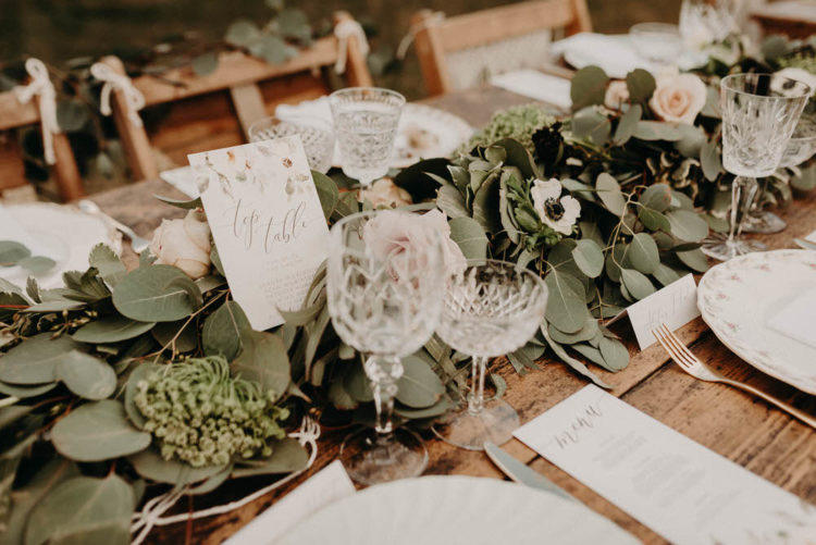 The wedding tablescape showed off a fresh greenery runner with blush blooms and floral table names