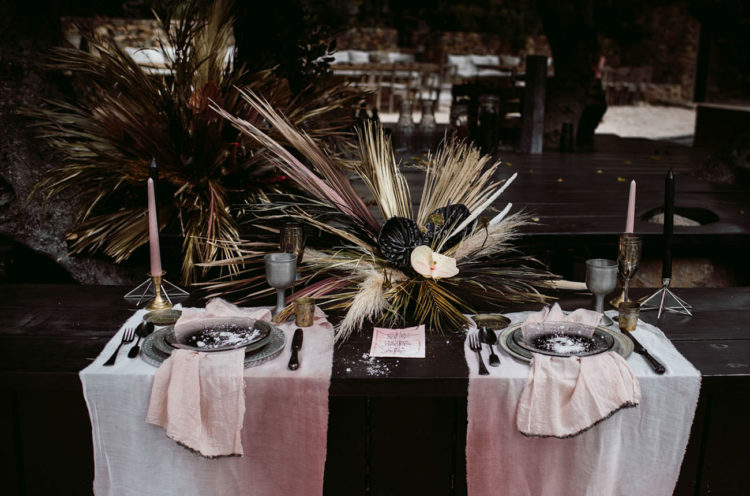 The wedding tablescape was done with a dark-stained table, ombre dyed pink placemats and napkins ples greys