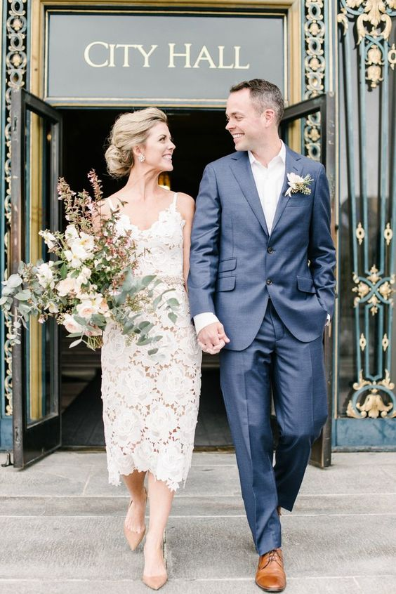 a floral lace sheath wedding dress on spaghetti straps, nude pumps and statement earrings